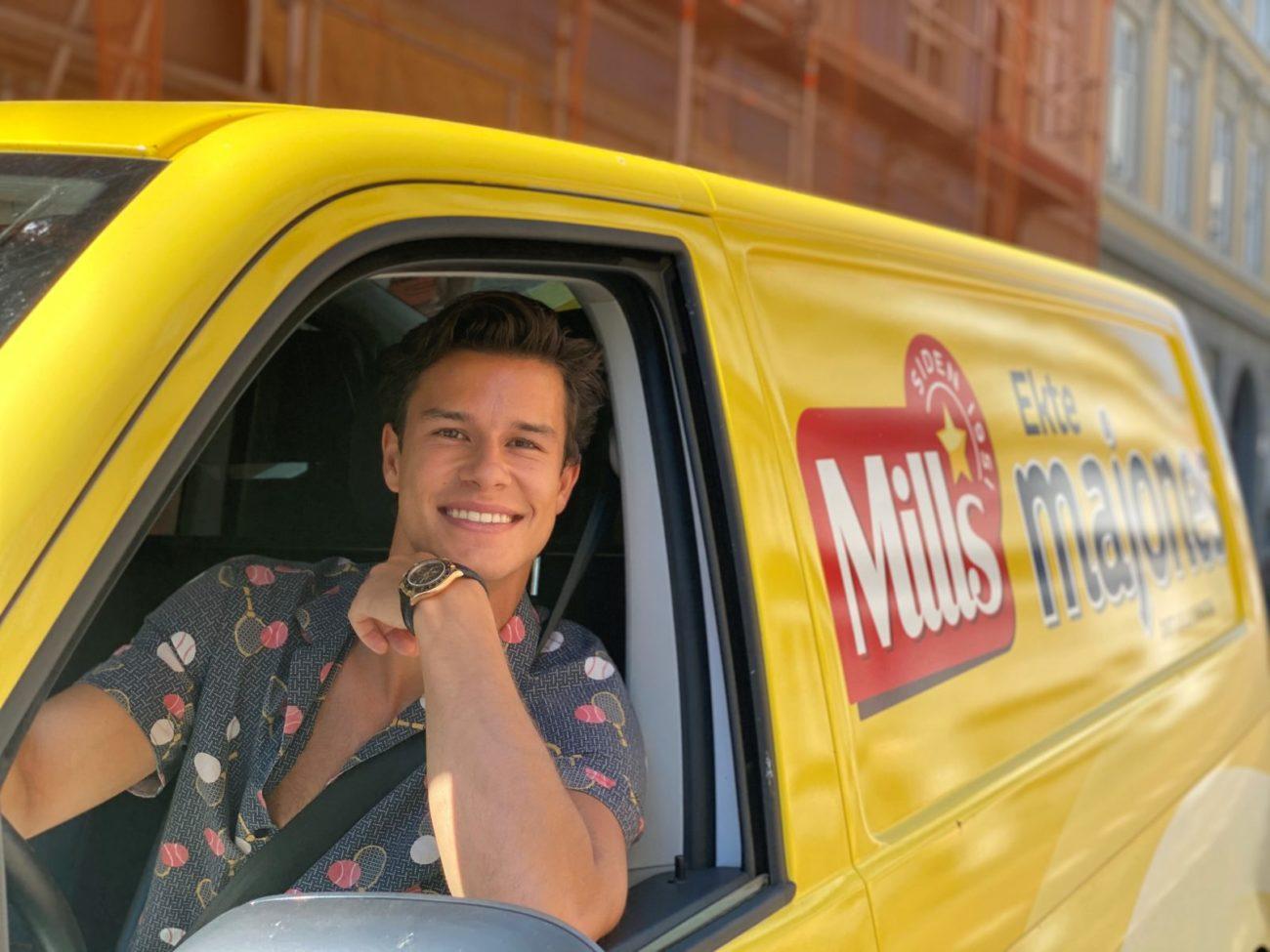 Summer intern Zakarias i gul Mills majones-bil. Foto.
