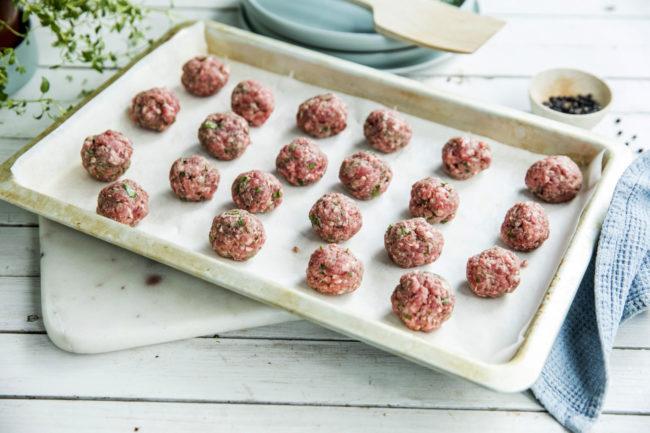 Rå kjøttboller på et stekebrett