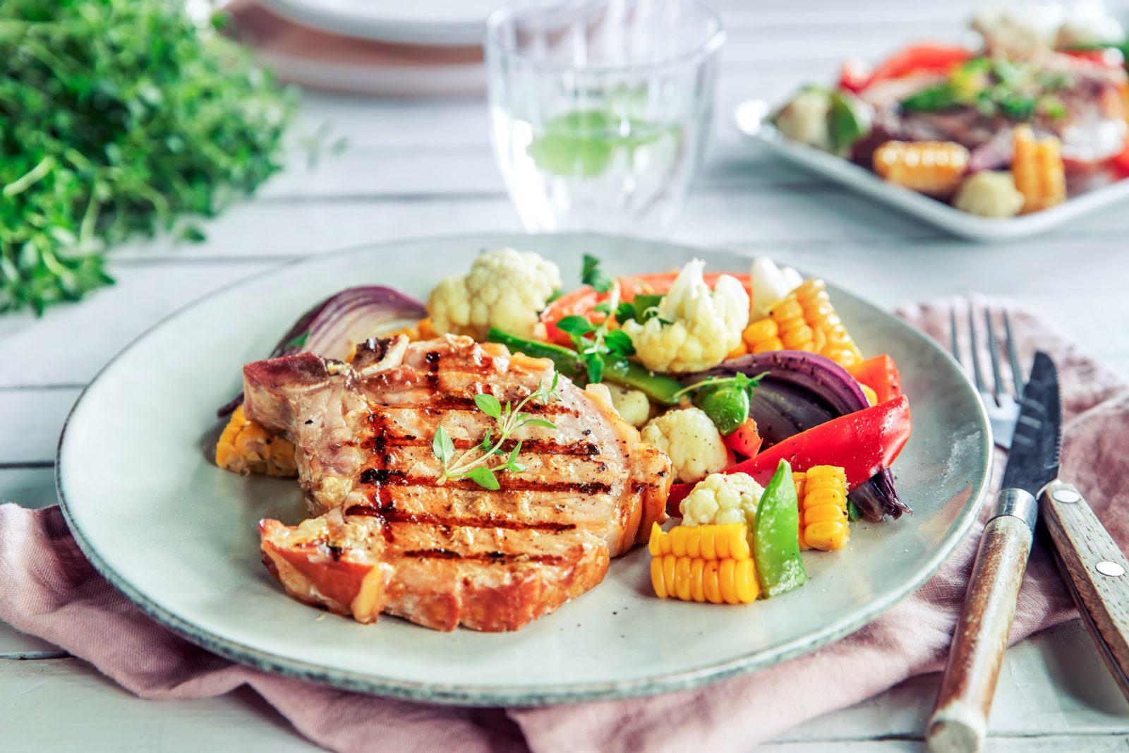 Sommerkoteletter med fargerik grønnsakspakke på grillen