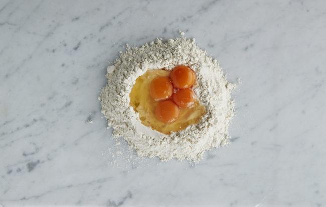 Hjemmelaget pasta - steg 1: mel med fire egg i fordypning