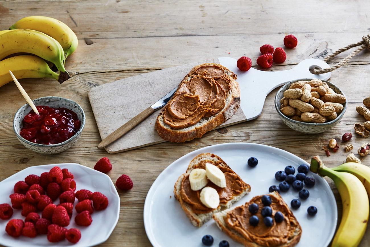 Peanøttsmør på brødskive med frukt og bær. Foto.