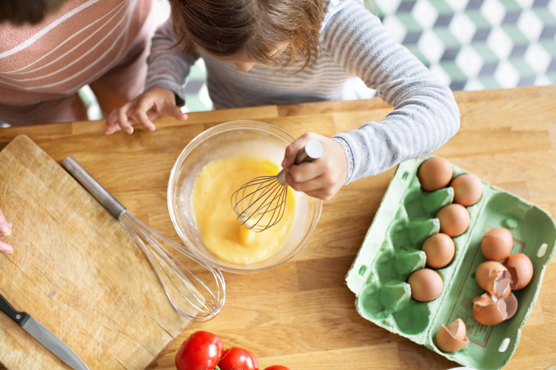 Jente som pisker egg til eggerøre. Foto.
