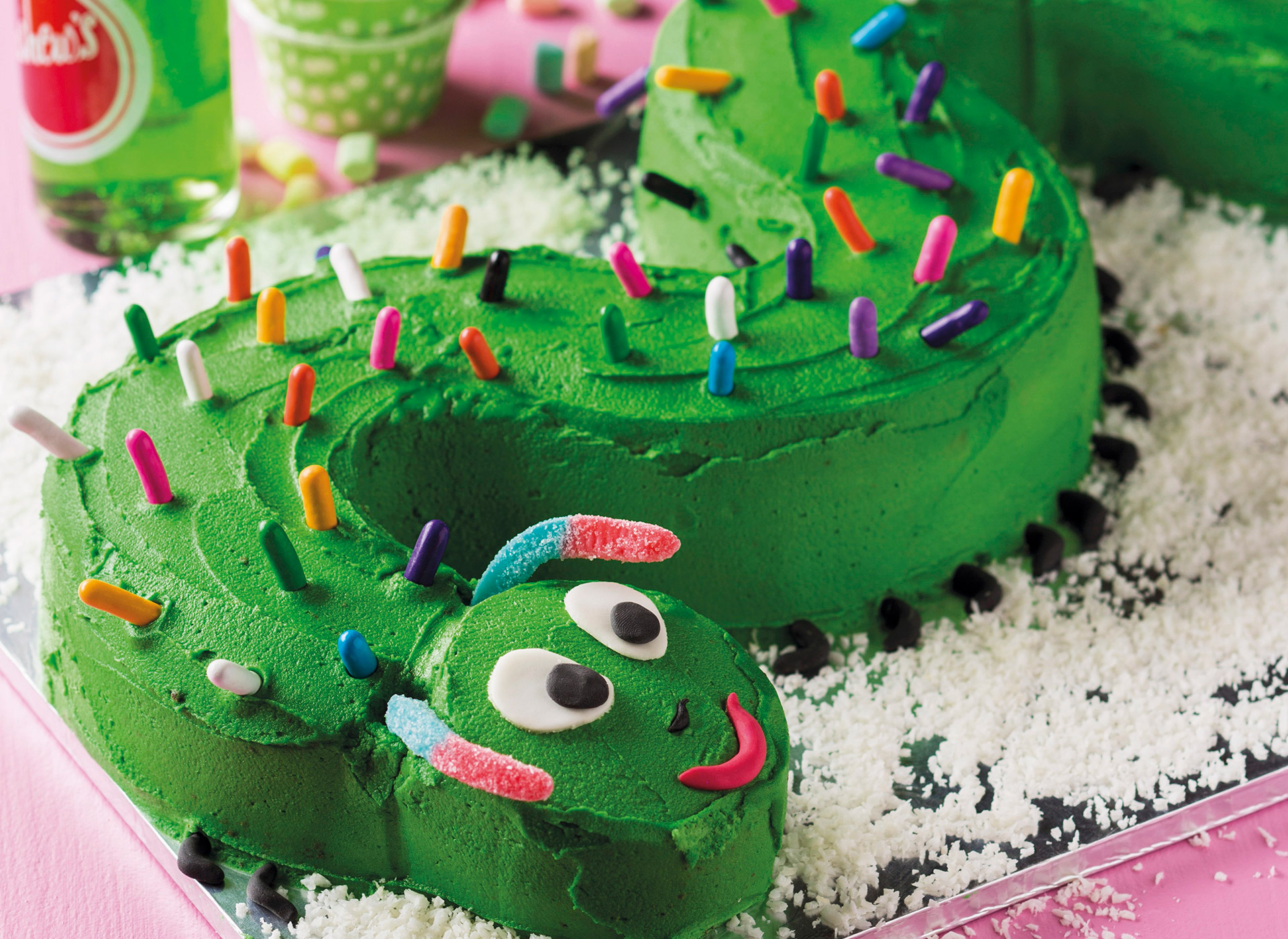 Bursdagskake formet som en grønn slange. Foto.