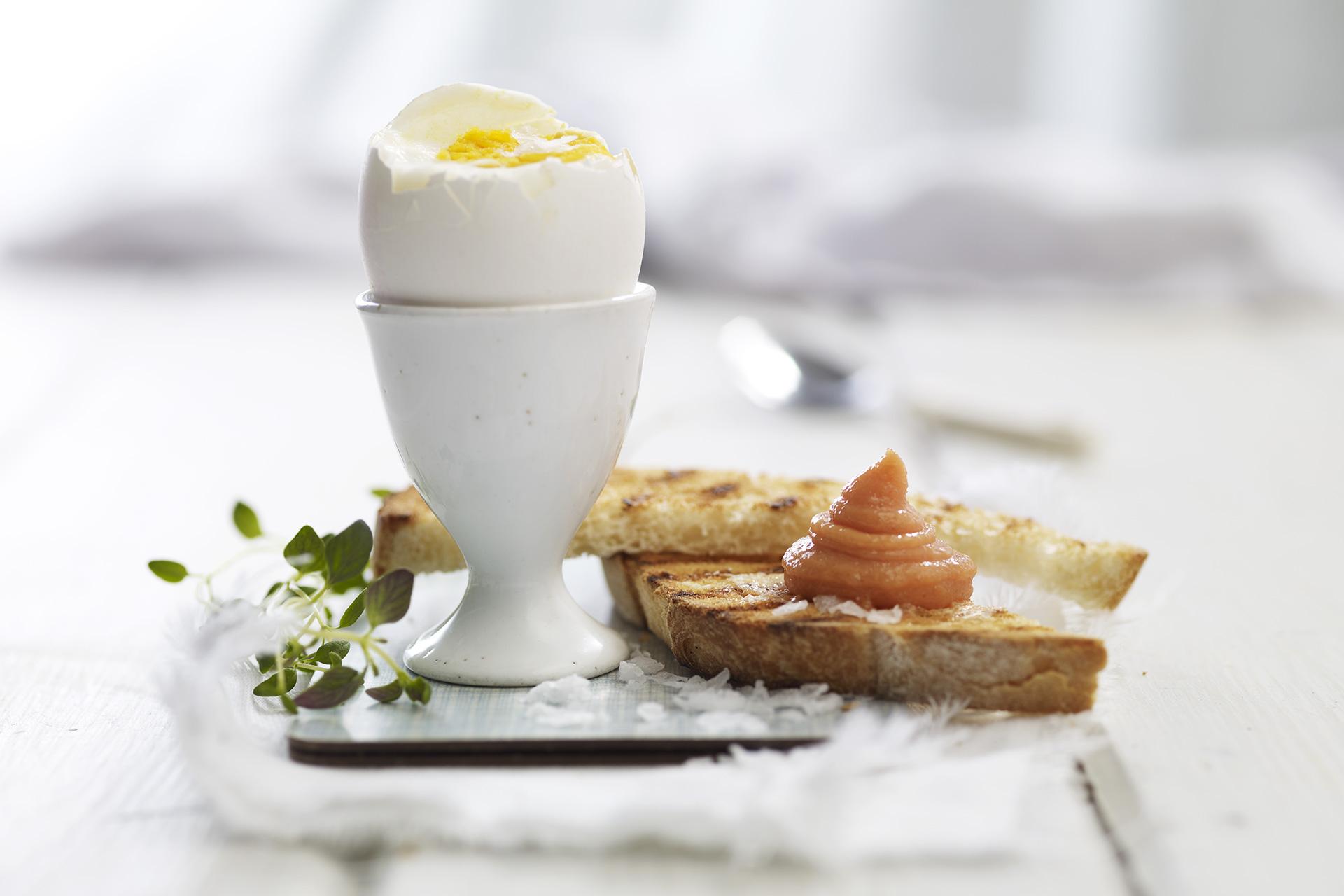Kokt egg med kaviar og brød. Foto.