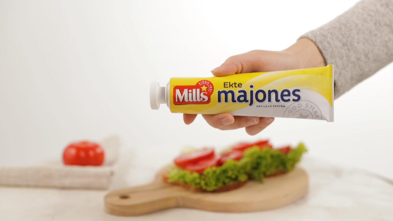 Hånd som holder opp tube med Mills majones - med ny kork