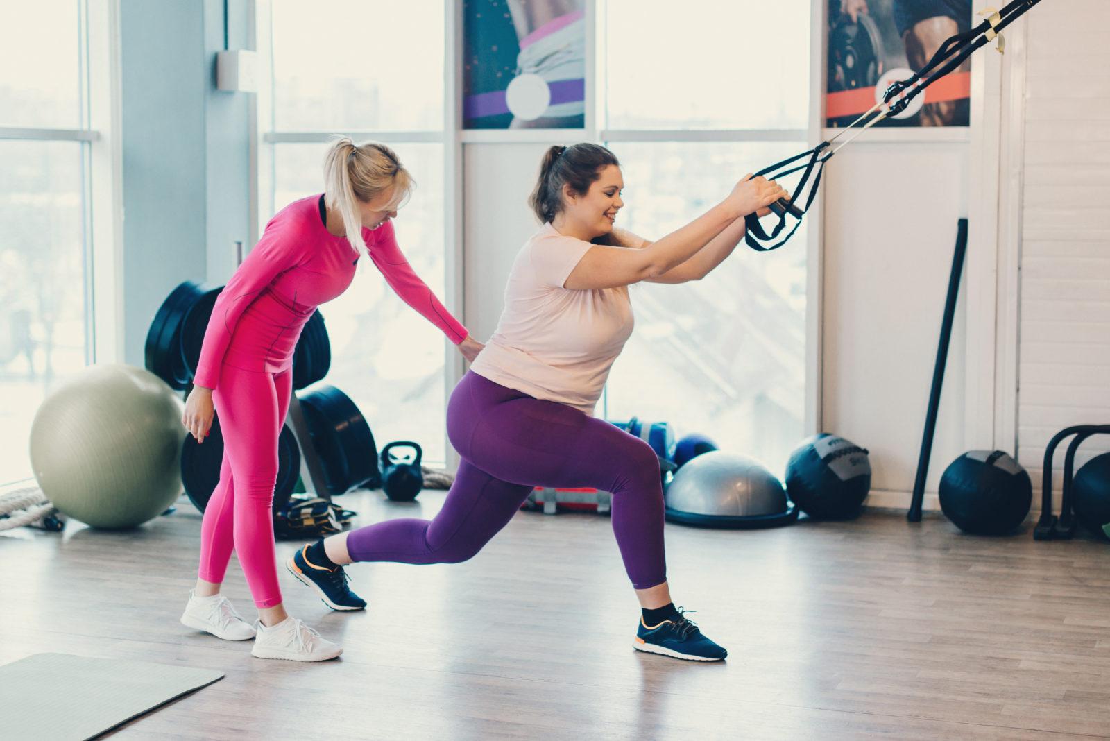 Treningsinstruktør og dame som trener styrke