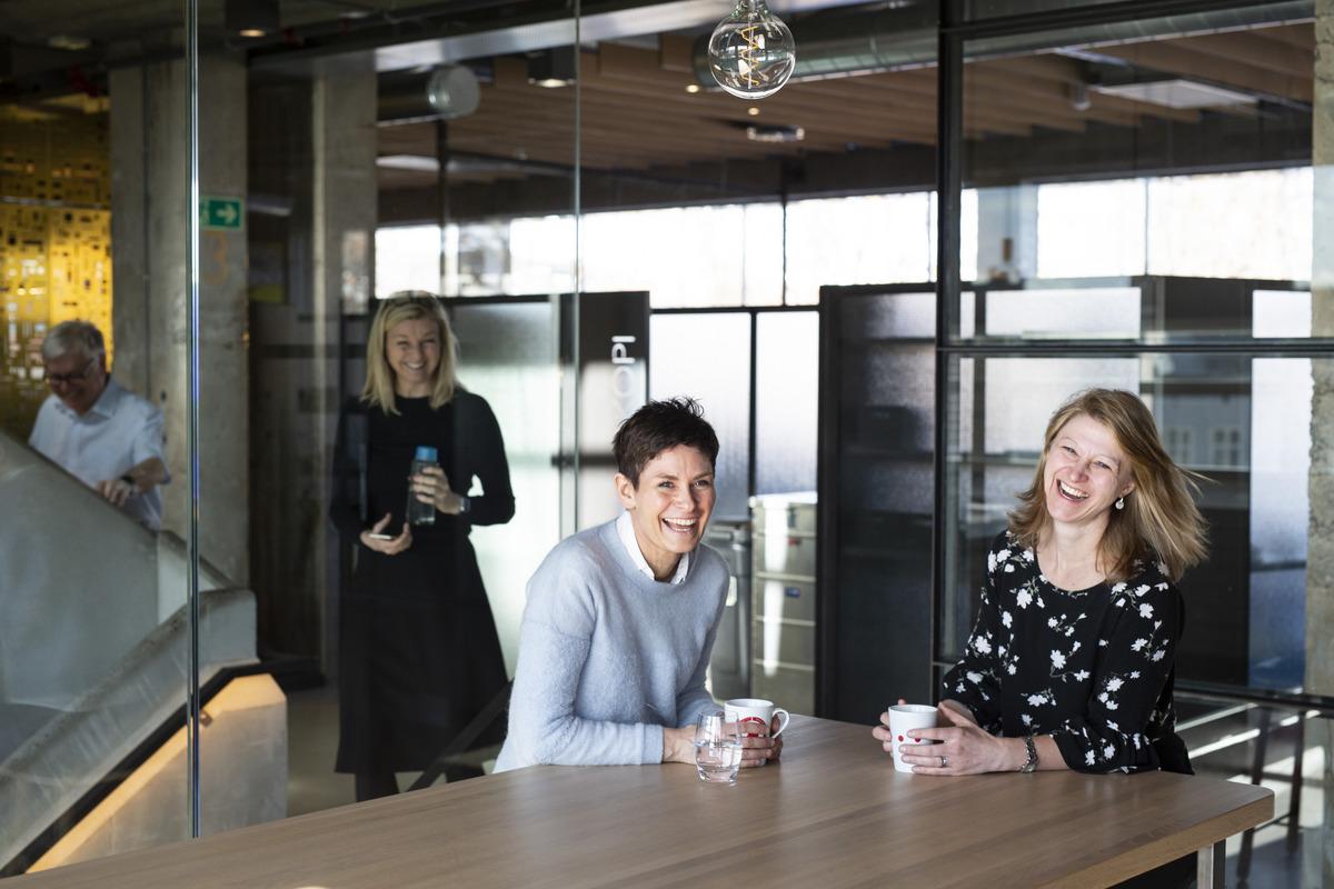 Ansatte i kontormiljø, to som smiler mens de drikker kaffe.foto