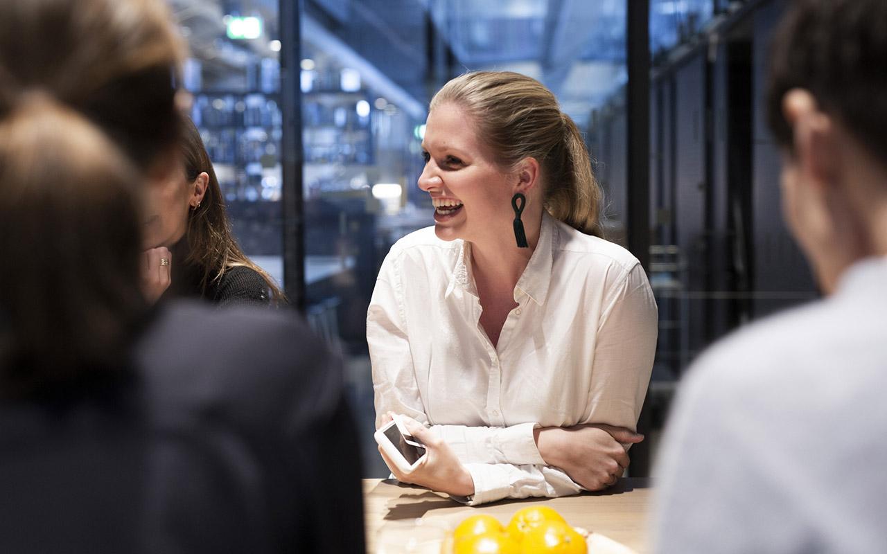 Kontoransatt smiler til kolleger. Foto.