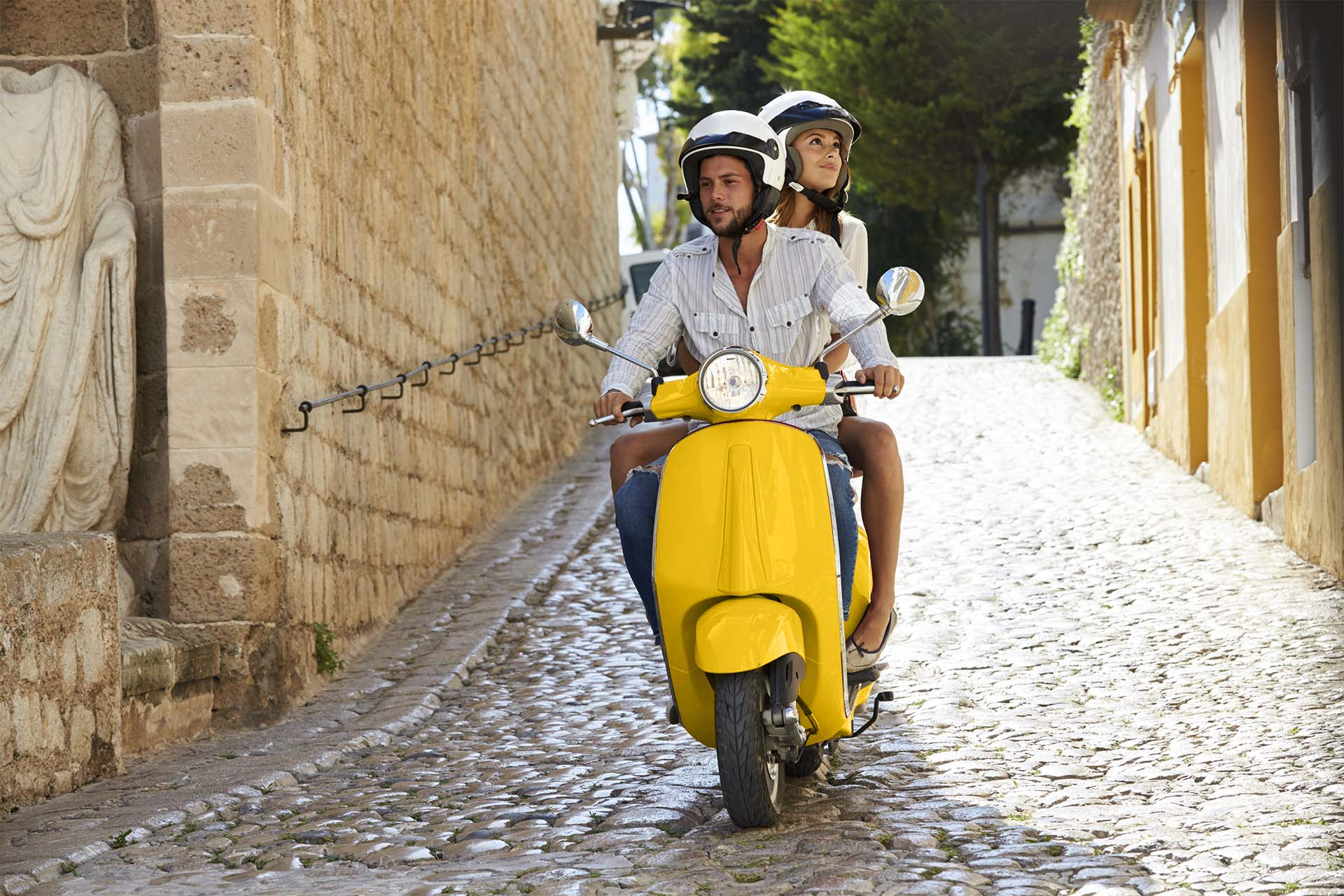 mann og dame på gul scooter i gate med brostein